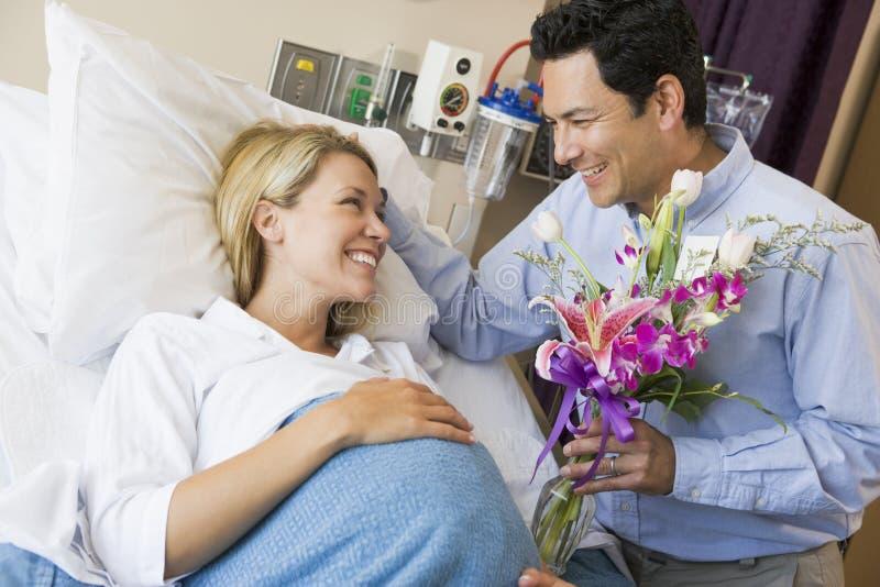 blommor som ger hans man den gravida frun royaltyfria foton