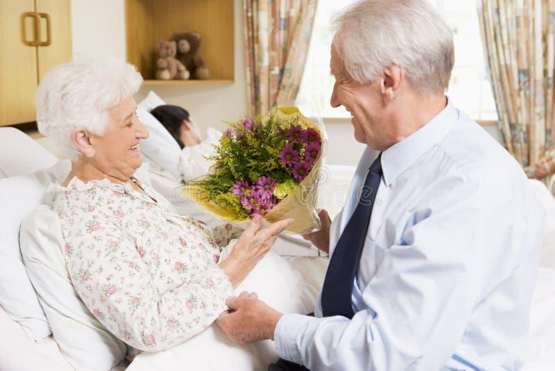 blommor som ger hans sjukhusmanpensionär till frun royaltyfri foto