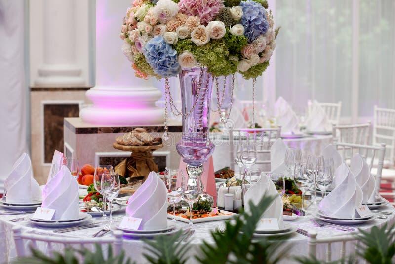 Blommor, vinexponeringsglas, servetter och sallad på tabellen royaltyfri fotografi