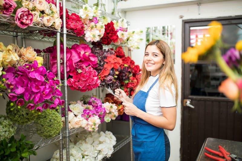 Blomsterhandelägare med en kontrollista royaltyfri bild