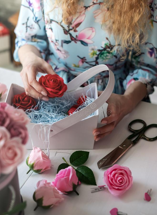 Blomsterhandel: blomsterhandlareflickan samlar en bukett av röda rosor i en blå pappers- korg royaltyfri foto