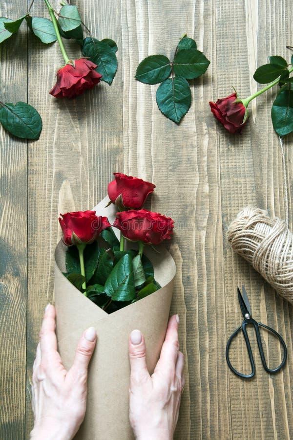 Blomsterhandlare göra röda rosor bukett som slår in i kraft papper på en trätabell ovanför sikt arkivbild