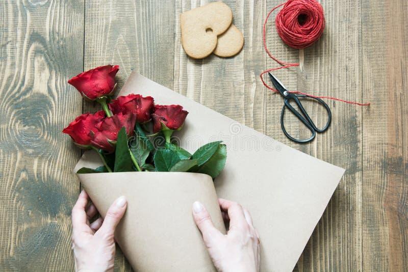 Blomsterhandlare göra röda rosor bukett som slår in i kraft papper på en trätabell ovanför sikt fotografering för bildbyråer