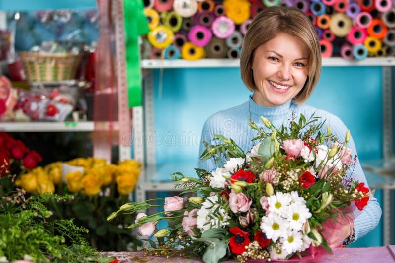 Blomsterhandlare i arbetsplatsen blommaillustrationen shoppar smellcomp le kvinna för härlig stående royaltyfri bild