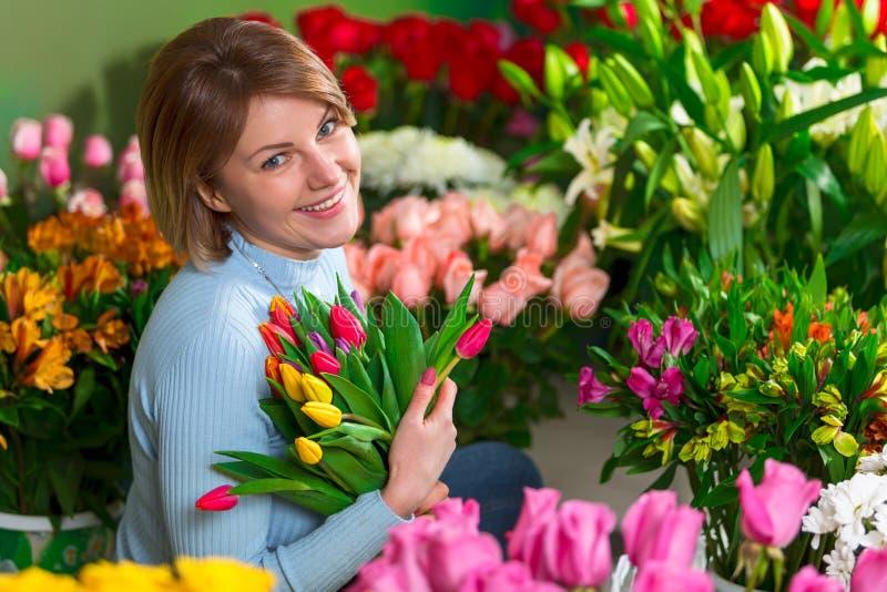 Blomsterhandlare i arbetsplatsen blommaillustrationen shoppar smellcomp le kvinna för härlig stående royaltyfri foto