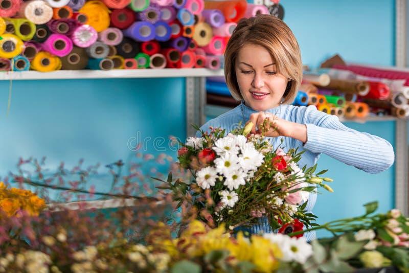 Blomsterhandlare i arbetsplatsen blommaillustrationen shoppar smellcomp le kvinna för härlig stående royaltyfri fotografi