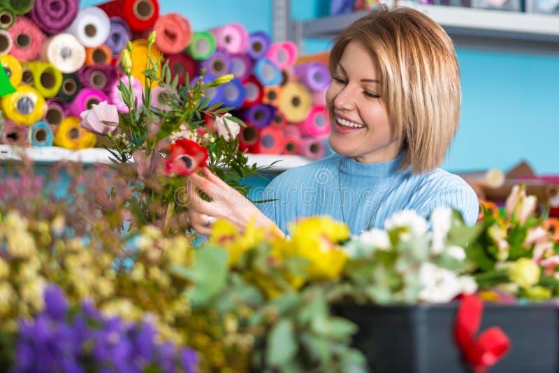 Blomsterhandlare i arbetsplatsen blommaillustrationen shoppar smellcomp Stående av en le kvinna arkivfoton