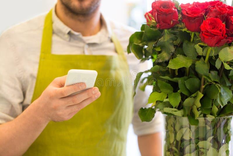 Blomsterhandlare med smartphonen och rosor på blomsterhandeln arkivbilder