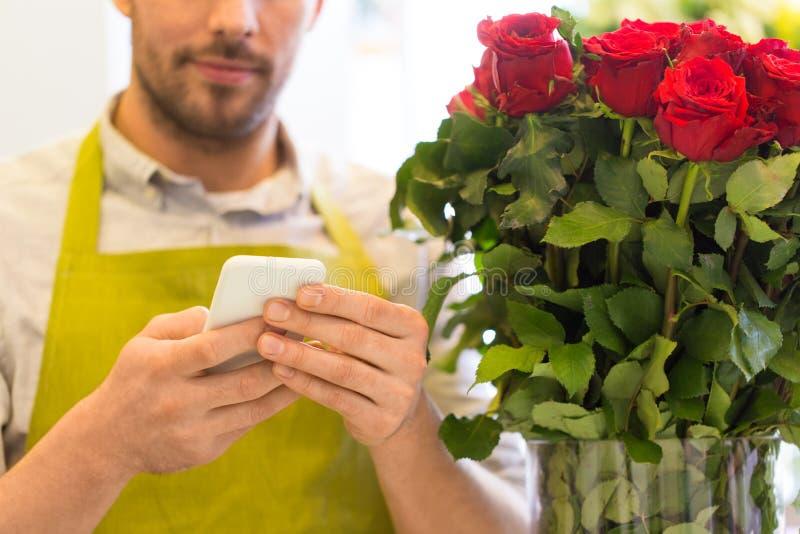 Blomsterhandlare med smartphonen och rosor på blomsterhandeln fotografering för bildbyråer