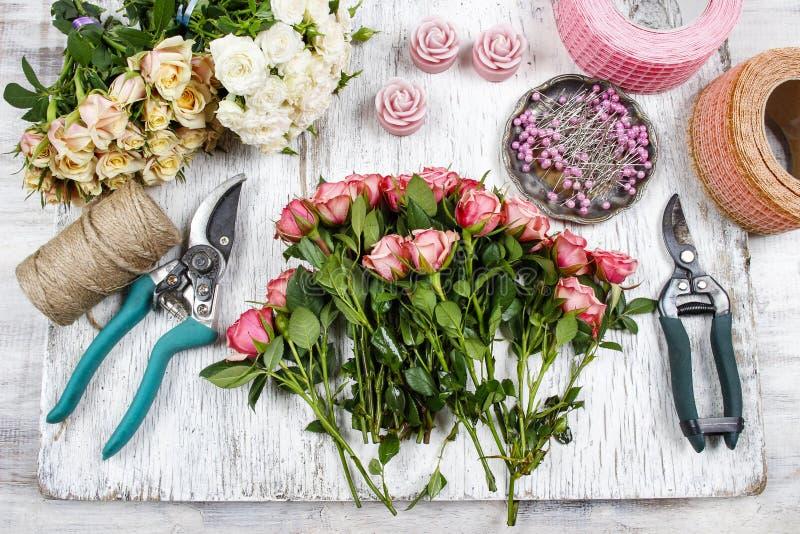 Blomsterhandlare på arbete Kvinnadanandebukett av rosa rosor arkivbilder