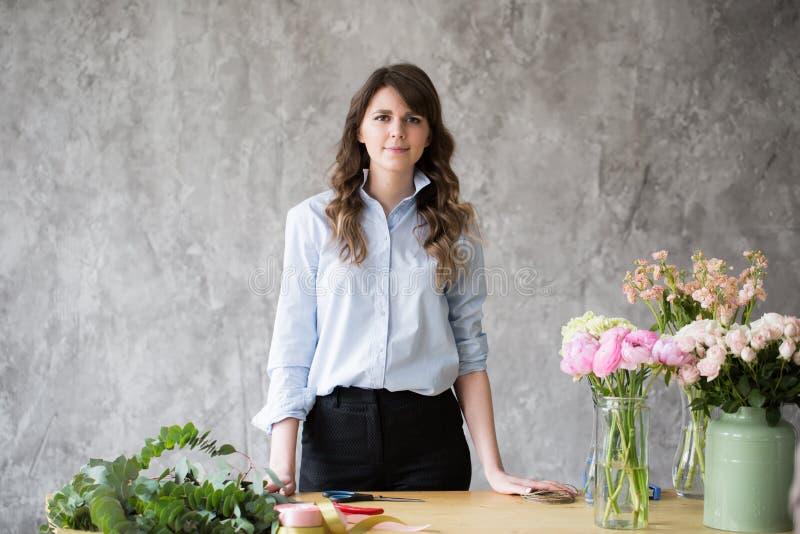 Blomsterhandlare på arbete: modern bukett för nätt danandemode för ung kvinna av olika blommor arkivfoto