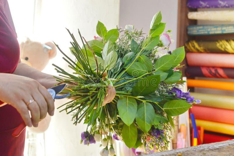 Blomsterhandlare p? arbete Kvinna som gör buketten av vårmattiolablommor royaltyfri bild