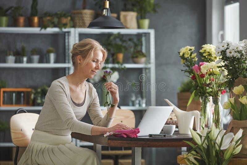 Blomsterhandlare som arbetar på hennes bärbar dator arkivfoton