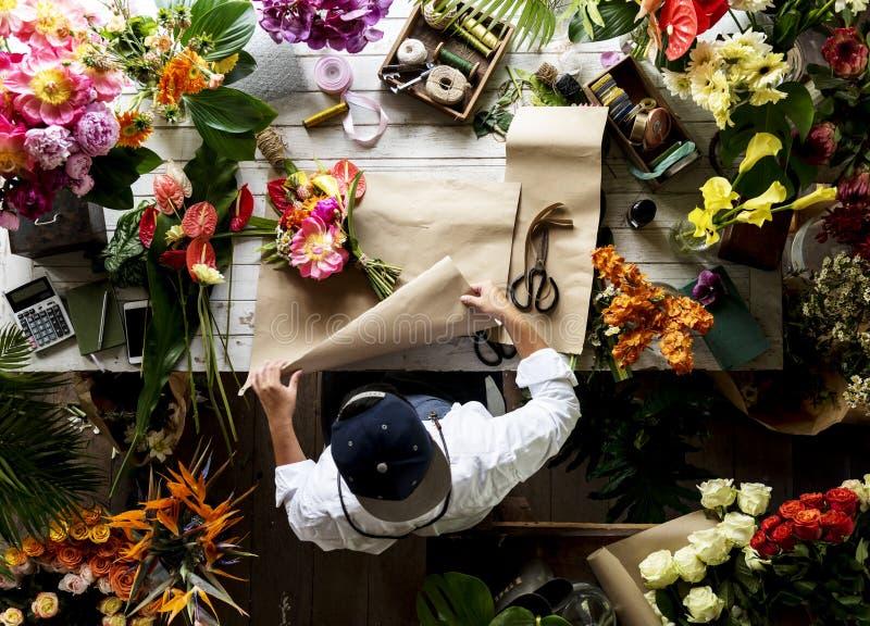 Blomsterhandlare som gör en blommaordning i en blomsterhandel arkivbild