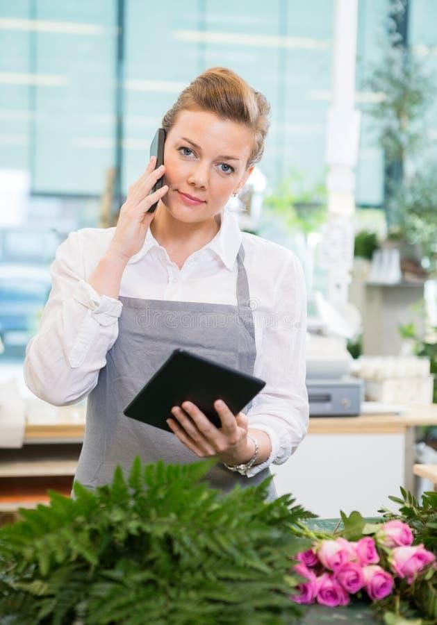 Blomsterhandlare Using Mobile Phone och Digital minnestavla in royaltyfria foton
