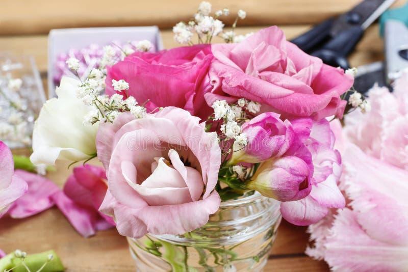 Blomsterhandlarearbetsplats: ofullständiga mycket små buketter i glass vaser arkivbild