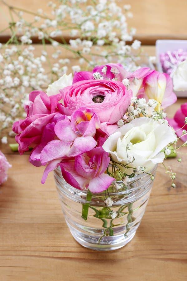Blomsterhandlarearbetsplats: ofullständiga mycket små buketter i glass vaser royaltyfria foton