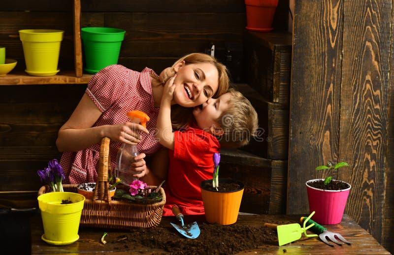 Blomsterhandlarebegrepp För kyssblomsterhandlare för liten unge som kvinna besprutar blomman Hem- blomsterhandlare på arbete Blom arkivfoton