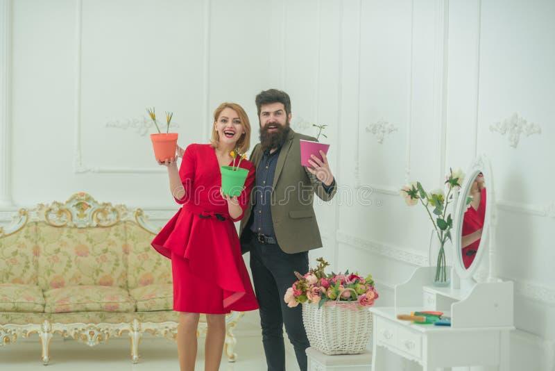 Blomsterhandlarebegrepp Lyckliga kvinna- och manblomsterhandlare ler med vårblommor Blomsterhandlaren shoppar Blomsterhandlare i  royaltyfri bild