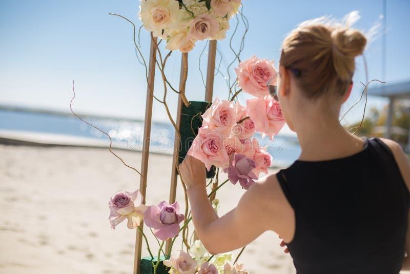 Blomsterhandlareflickan dekorerar att gifta sig bågen med nya blommor på den sandiga kusten av sjön Gifta sig blomsterhandlaredek arkivfoto