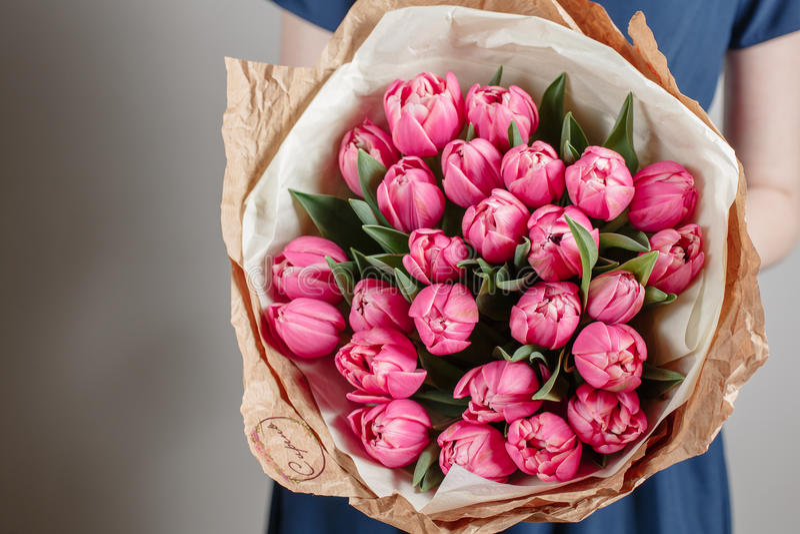 Blomsterhandlareflickan med pionen blommar eller den rosa buketten för blomman för den unga kvinnan för tulpan för födelsedagmode arkivbilder