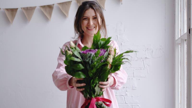 Blomsterhandlareflickan ser kameran och visar buketten Stående i en blomsterhandel arkivbild