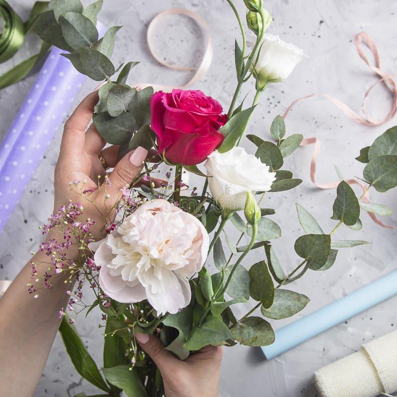 Blomsterhandlarehj?lpmedel och arbetsplats med band, blommor och sax royaltyfria bilder