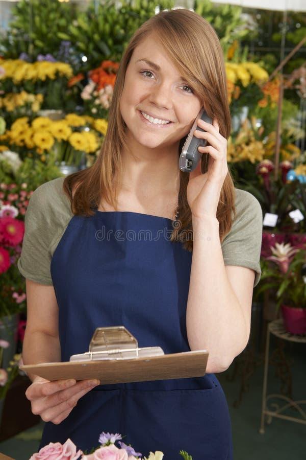 BlomsterhandlareIn Shop Holding skrivplatta som tar telefonbeställning royaltyfria foton