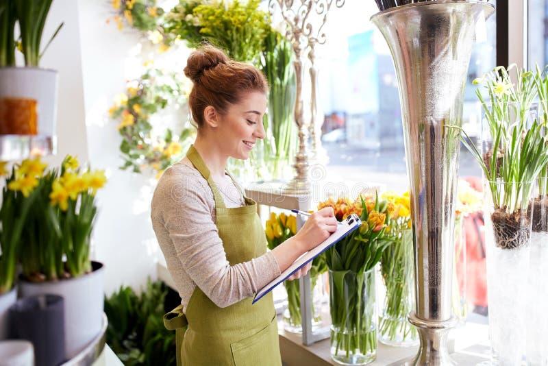 Blomsterhandlarekvinna med skrivplattan på blomsterhandeln royaltyfri bild