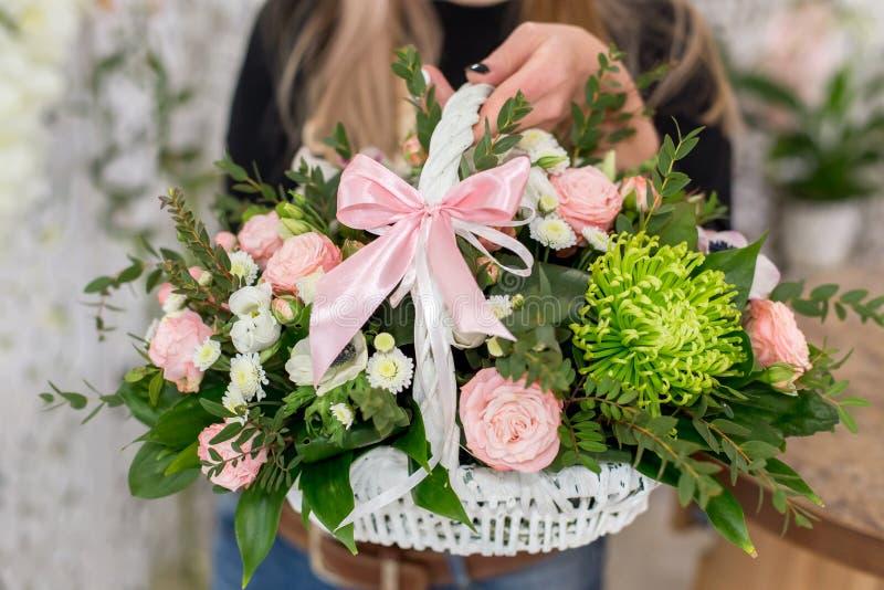 Blomsterhandlarekvinna som rymmer en härlig bukett av rosor i den vita korgen arkivfoton