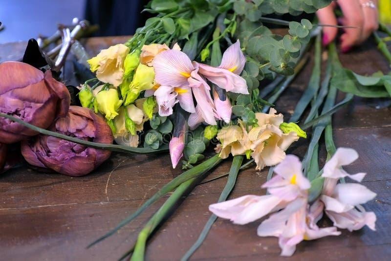 Blomsterhandlarekvinnan gör buketten av eustoma, brun pion och irins i blomsterhandel royaltyfria foton