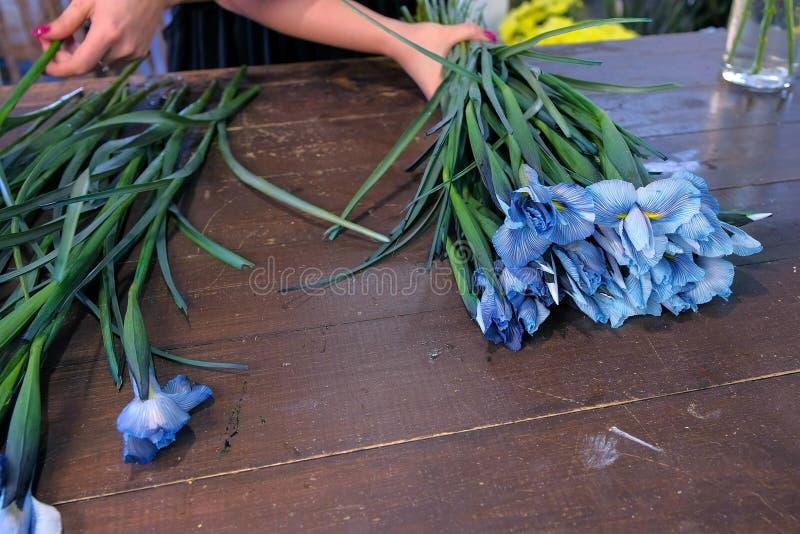 Blomsterhandlarekvinnan som gör buketten från blåa irisblommor på tabellen till salu shoppar in royaltyfria bilder