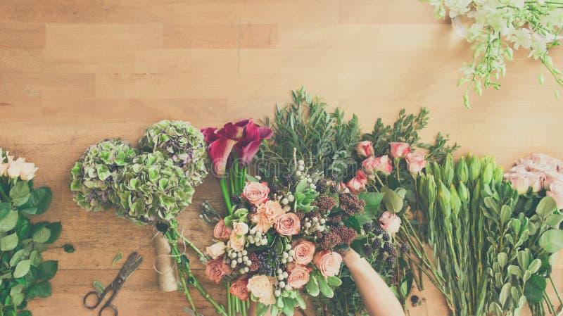 Blomsterhandlaren i blomsterhandelleverans gör den rosa buketten, bästa sikt för tabell arkivfoton