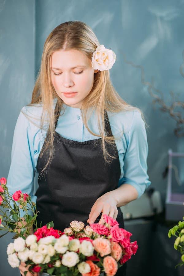 Blomsterhandlaren som väljer buketten för röda rosor på, shoppar marknaden royaltyfria bilder