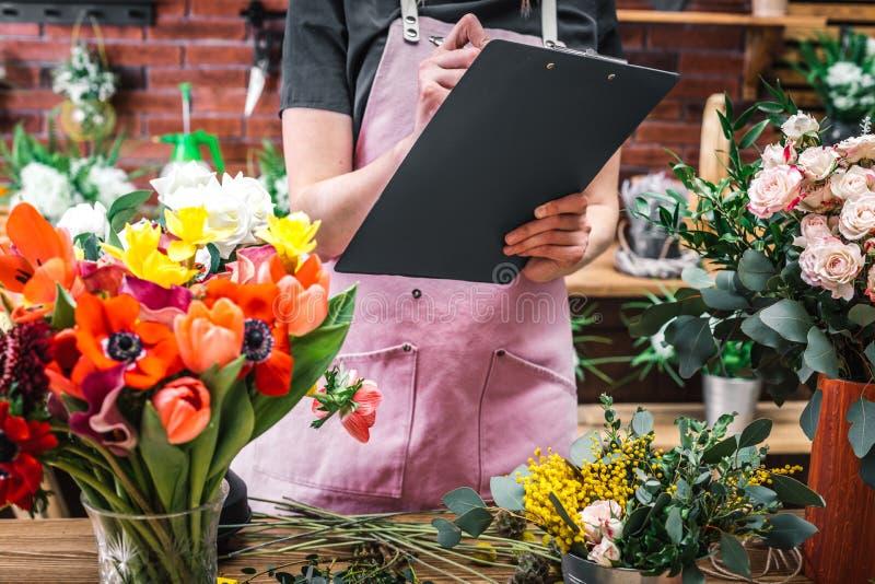 Blomsterhandlareräkningar och antecknar blommor arkivbilder
