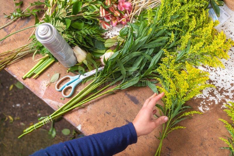 Blomsterhandlareworktable Blomsterhandlare på arbete som skapar buketten på blomsterhandeln Top beskådar royaltyfri fotografi