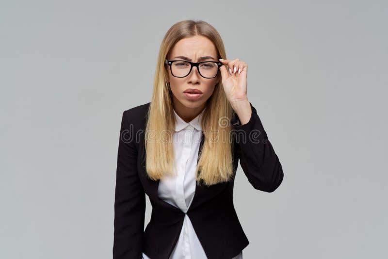 Blond affärskvinna i en dräkt och exponeringsglas som plirar hållande exponeringsglas med en framåt hand och benägenhet royaltyfria bilder