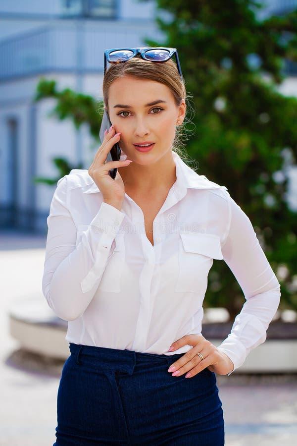Blond affärskvinna som kallar på mobiltelefonen i stadsgata royaltyfri foto