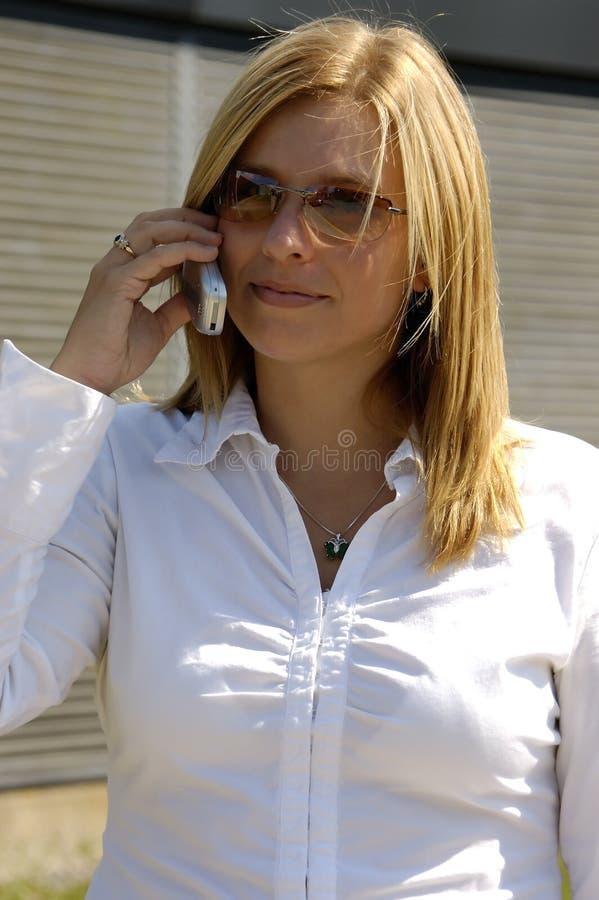 Blond auf einem Handy lizenzfreie stockfotos