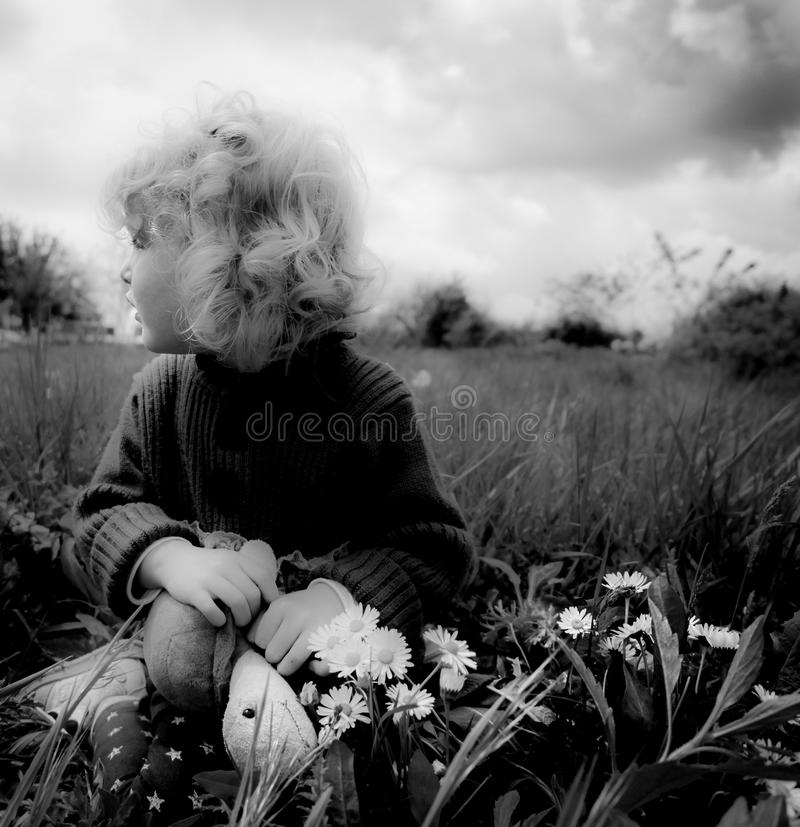 Blond baby girl with turtle on the grass stock photo