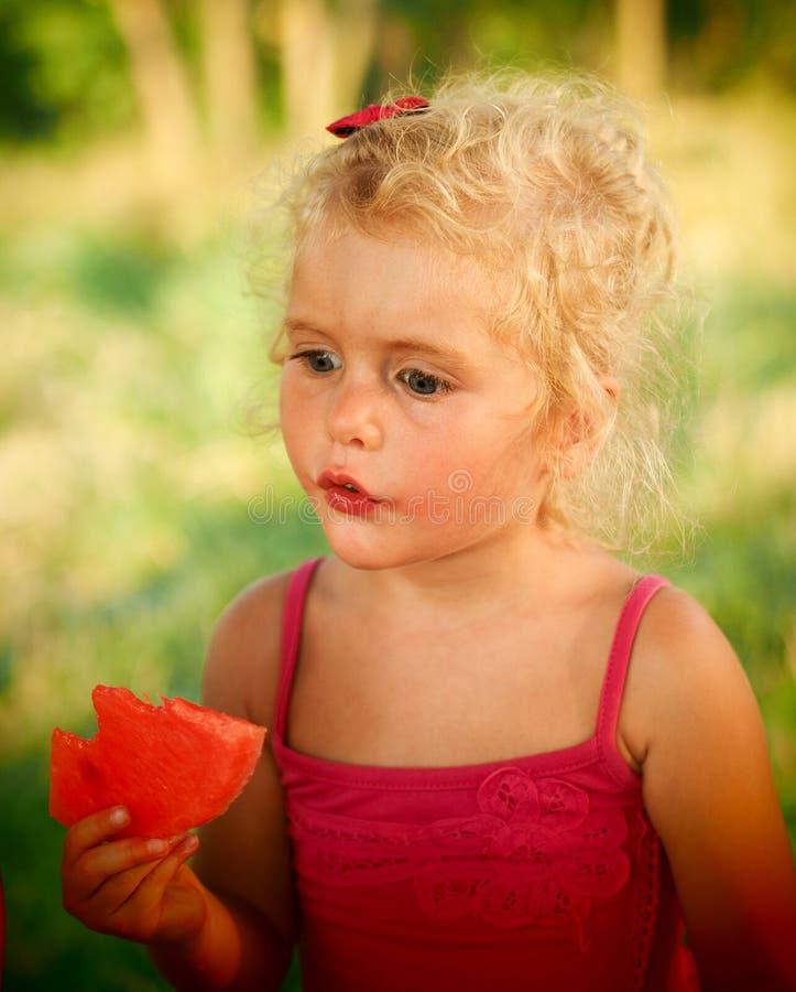 Blond babymeisje die watermeloen eten stock afbeelding