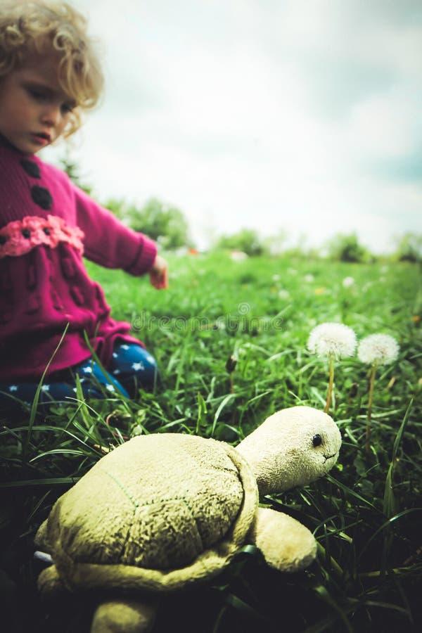 Blond babymeisje met schildpad op het gras royalty-vrije stock afbeelding