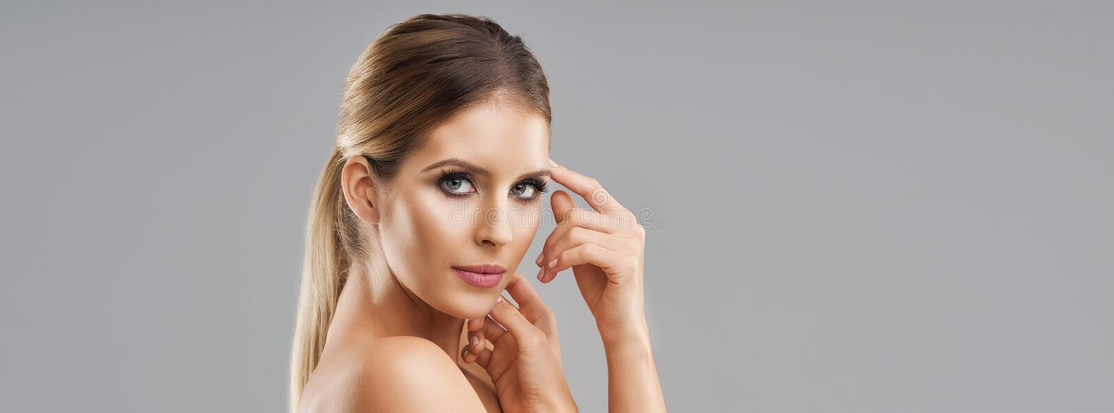 Beautiful adult woman posing over gray background stock photos