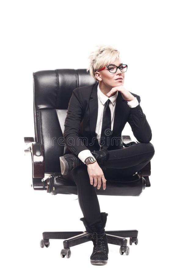 Blond beautiful business lady in white shirt eyeglasses black su. It and black tie sit on chair stock photo