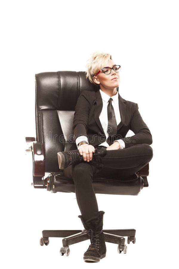 Blond beautiful business lady in white shirt eyeglasses black su. It and black tie sit on chair royalty free stock photo