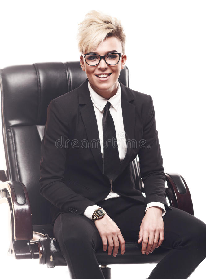 Blond beautiful business lady in white shirt eyeglasses black su. It and black tie sit on chair royalty free stock image