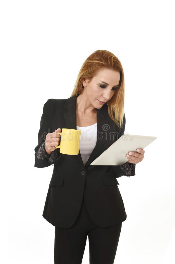 Blond beautiful businesswoman holding digital tablet pad drinking coffee looking thoughtful royalty free stock photos