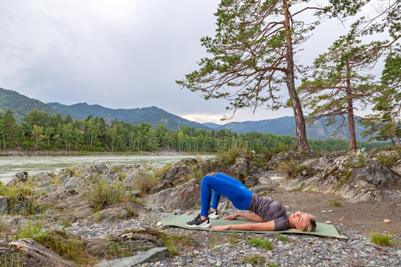 Blond beautiful girl is making a warm-up lying on the stone ground in the pose of the bridge, resting his palms and shoulder royalty free stock images
