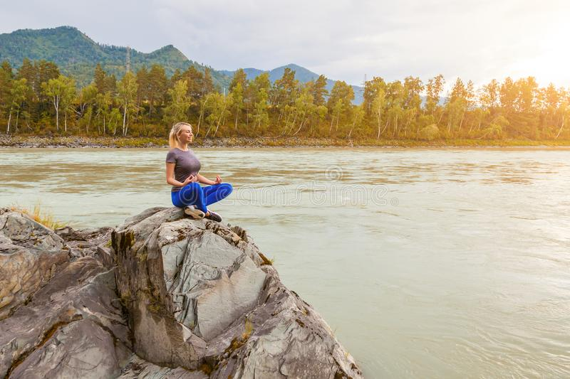 Blond beautiful girl sitting on the stone cliff ground resting after sport and doing yoga and meditation outdoors in the mountains royalty free stock photo