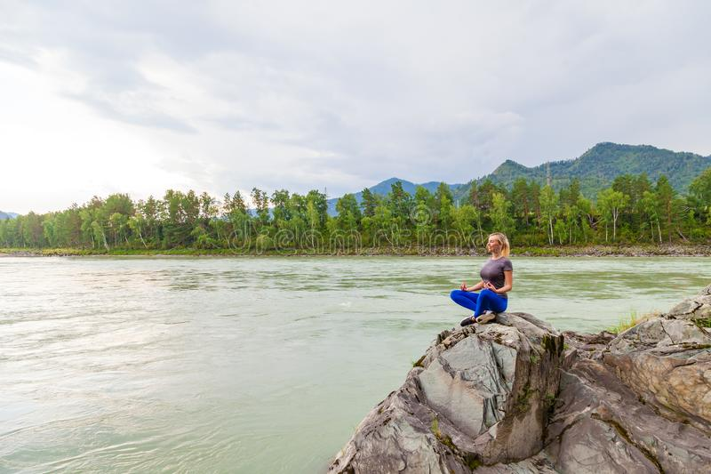 Blond beautiful girl sitting on the stone cliff ground resting after sport and doing yoga and meditation outdoors in the mountains royalty free stock image